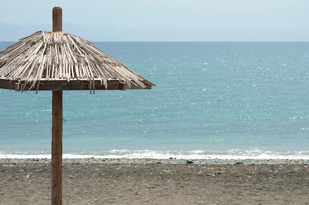 Cartão postal de verão. guarda-chuva de palha na areia, mar azul e dia de verão.