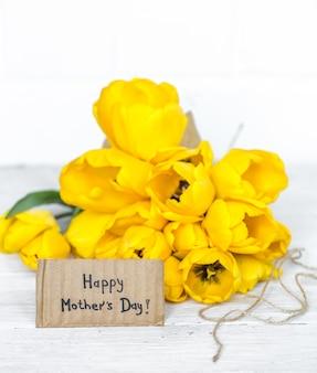 Cartão postal dia das mães e tulipas amarelas na madeira