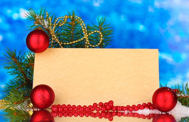 Cartão postal em branco, bolas de natal e pinheiro em fundo azul