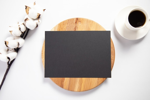 Cartão preto com um galho de algodão e café