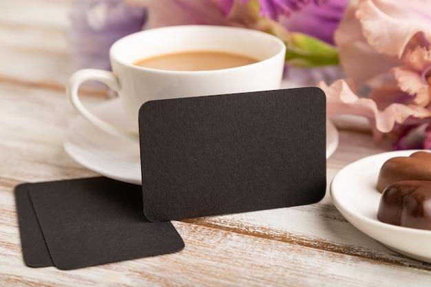 Cartão preto com uma xícara de café, bombons de chocolate e flores de íris em fundo branco.