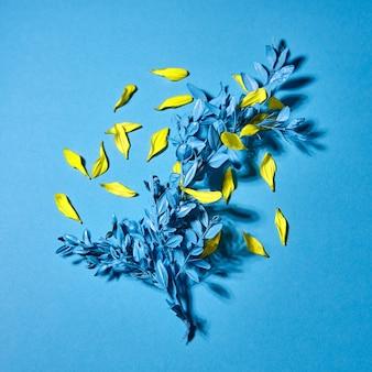 Cartão romântico com ramo de planta de folha azul e pétalas de flores amarelas sobre fundo azul com espaço de cópia. vista do topo.