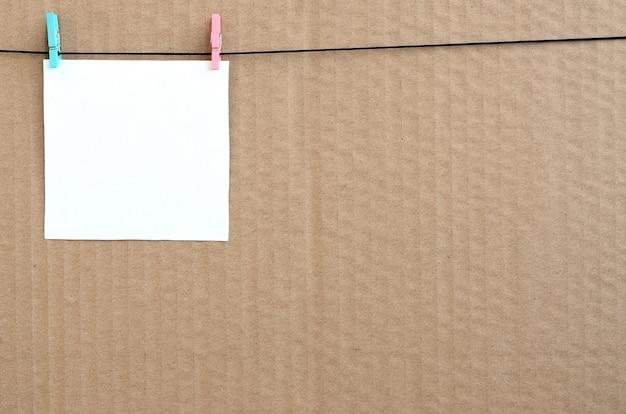 Cartão vazio branco na corda em um fundo marrom do cartão.