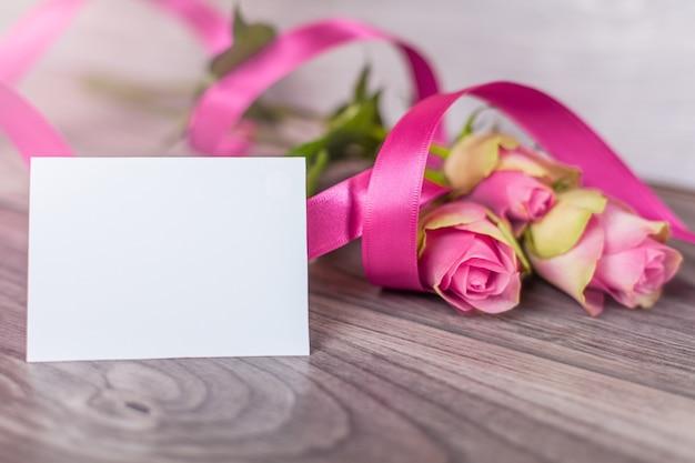 Cartão vazio com rosas na madeira