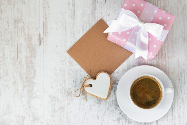 Cartão vazio com uma caixa de presente, biscoito de amor em forma de coração e uma xícara de café.