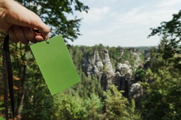 Cartão verde nas mãos dos homens no fundo do parque nacional da suíça saxônica, alemanha.