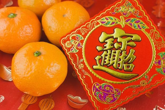 Cartão vermelho com uma tangerina para comemorar o ano novo chinês