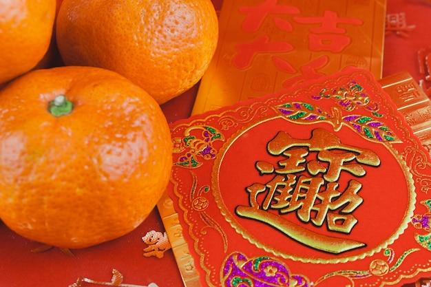 Cartão vermelho e dourado com uma tangerina para comemorar o ano novo chinês