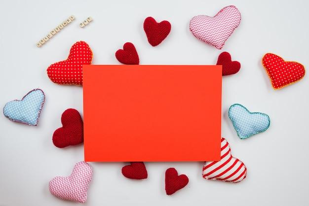 Cartão vermelho para escrever desejos em uma superfície com corações