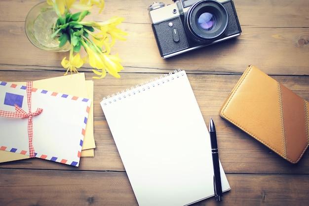 Cartas, câmera, caneta, papel, bloco de notas e flores na mesa de madeira