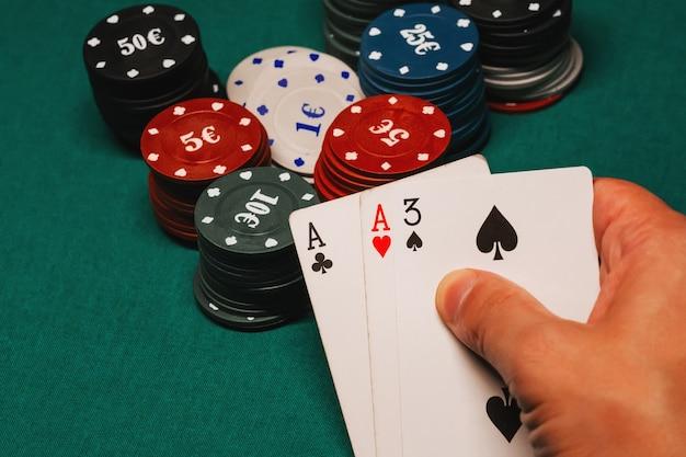 Cartas com um par de ases nas mãos de um jogador de poker em um cassino no fundo de uma mesa com fichas