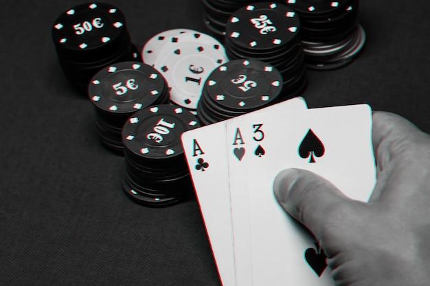 Cartas com um par de ases nas mãos de um jogador de pôquer em um cassino na mesa com fichas. foto em preto e branco com efeito de falha
