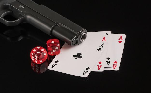 Cartas, dados e uma arma em um fundo preto. o conceito de jogos de azar e entretenimento. cassino e pôquer