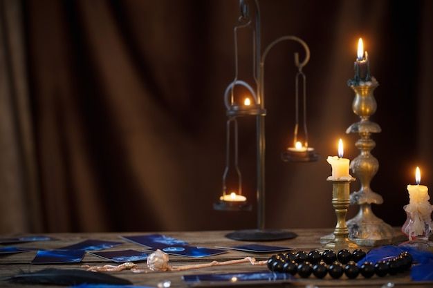 Cartas de adivinhação e velas acesas em uma mesa de madeira