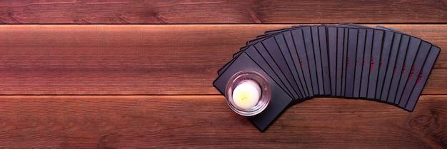 Cartas de adivinhação em uma mesa de madeira com uma vela com lugar para texto. conceito de adivinhação, cartas de tarô, vidente.