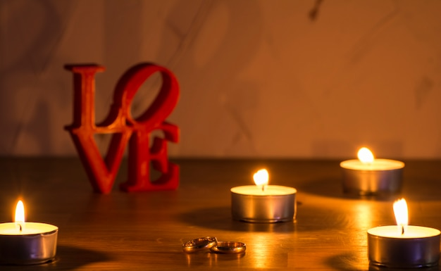 Cartas de amor vermelhas sobre fundo branco, à esquerda, com dois anéis e velas