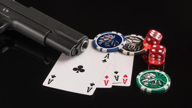 Cartas de fichas de pôquer e uma arma em um fundo preto o conceito de jogos de azar e entretenimento