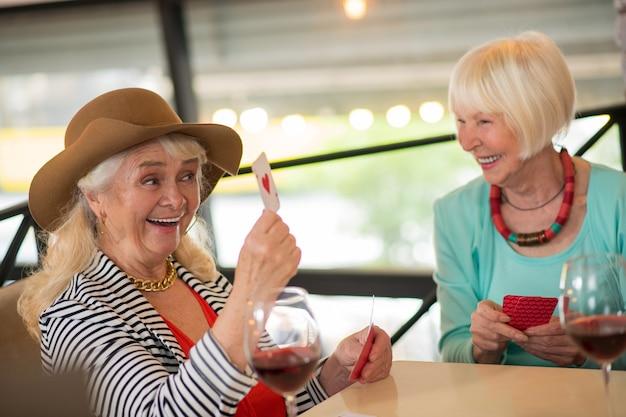 Cartas de jogar. mulheres sêniors alegres jogando cartas e parecendo animadas