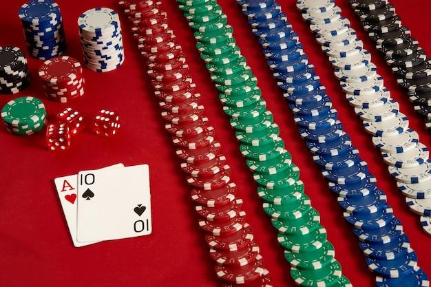 Cartas de pôquer e fichas de jogo em fundo vermelho. vista do topo. copie o espaço. ainda vida. postura plana. cartas - ás e dez