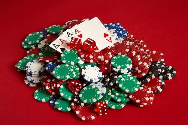 Cartas de pôquer e fichas de jogo em fundo vermelho. vista do topo. copie o espaço. ainda vida. postura plana. cartas - quatro ases. 4 de um tipo