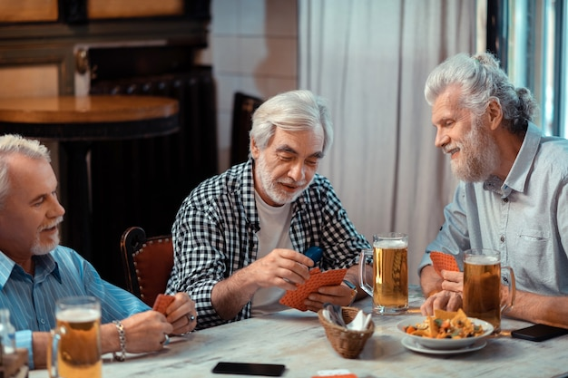 Cartas e cerveja. três aposentados jogando cartas enquanto bebiam cerveja juntos no bar