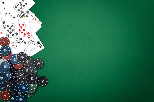 Cartas e fichas de pôquer em um fundo verde.