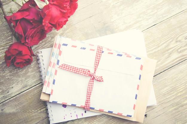Cartas e rosas sobre fundo de madeira