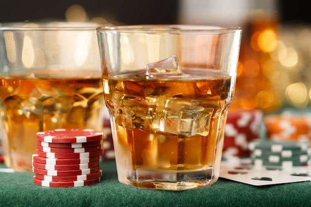 Cartas jogando fichas e álcool em copo
