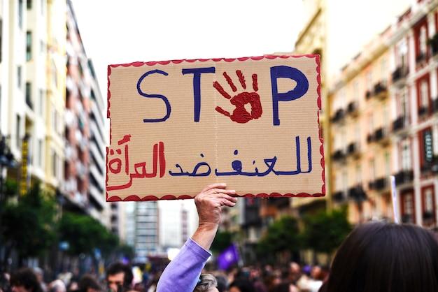 Cartaz anexado por um manifestante com a palavra stop em inglês e árabe durante uma demonstração