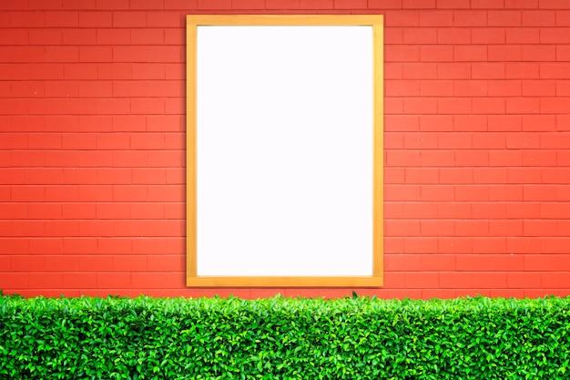 Cartaz branco com o modelo de moldura de madeira na parede de tijolo vermelho. brincar.