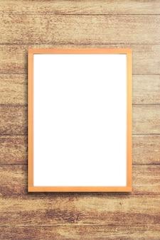 Cartaz branco com o modelo de moldura de madeira no fundo da parede de madeira. brincar.