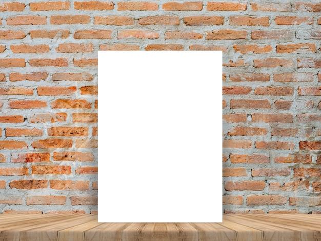 Cartaz branco em branco inclinado na mesa de madeira tropical com parede de tijolos