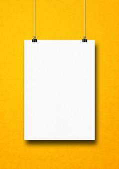 Cartaz branco pendurado em uma parede amarela com clipes
