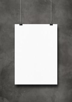 Cartaz branco pendurado em uma parede de concreto escura com clipes