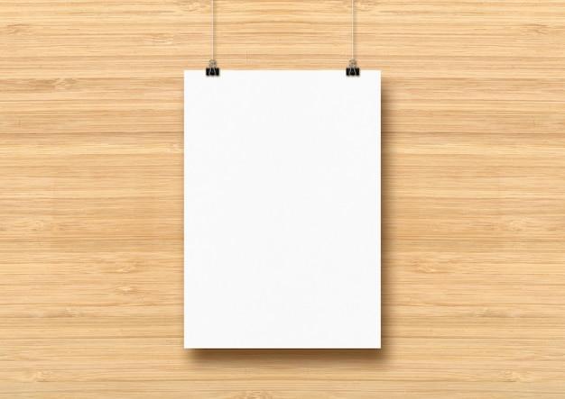 Cartaz branco pendurado em uma parede de madeira com clipes