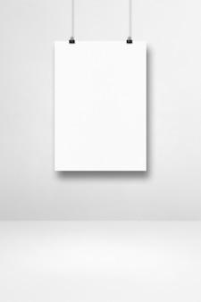 Cartaz branco pendurado em uma parede limpa com clipes. modelo de maquete em branco