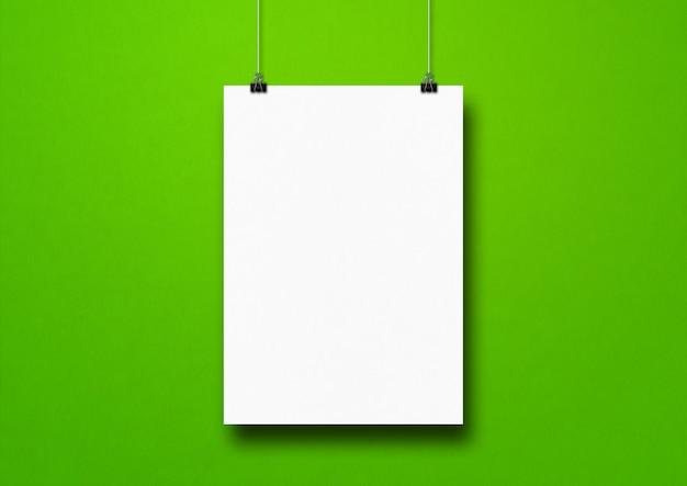 Cartaz branco pendurado em uma parede verde com clipes