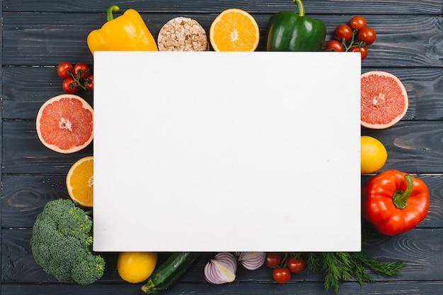 Cartaz branco sobre os legumes coloridos na mesa de madeira preta