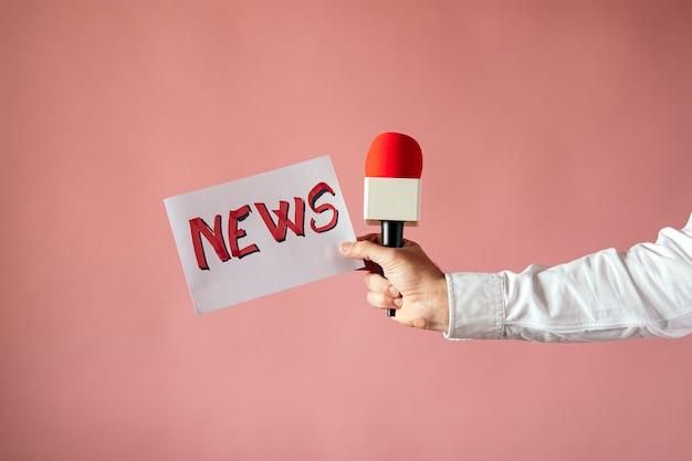 Cartaz com a palavra da notícia e microfone na mão do repórter com parede rosa
