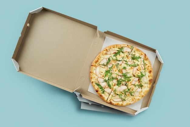 Cartaz conceitual para entrega de comida e pizza. pizza de carne em uma caixa de papelão para entrega em uma superfície azul com lugar para texto