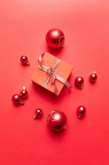 Cartaz criativo de natal com caixa de presente vermelha, fitas, bolas grandes e pequenas vermelhas, decorações do feriado em vermelho. vista plana, vista superior, copyspace
