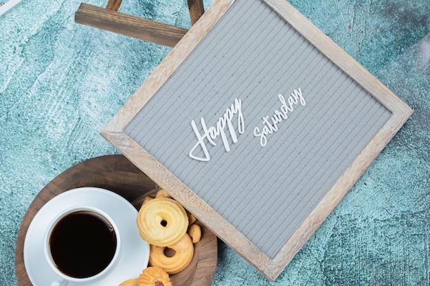 Cartaz de feliz sábado com biscoitos e um copo de bebida