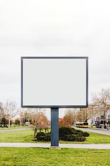 Cartaz de outdoor vertical rua em branco na grama verde na estrada da cidade