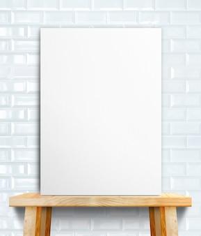 Cartaz de papel branco em branco na mesa de madeira na parede de azulejo branco