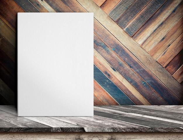 Cartaz de papel branco em branco na mesa de madeira na parede de prancha de madeira diagonal