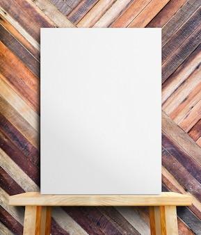 Cartaz de papel branco em branco na mesa de madeira na parede tropical de madeira diagonal