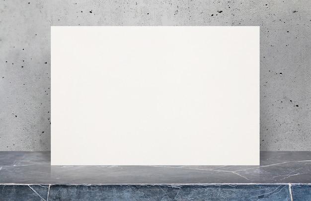 Cartaz de papel branco em branco na mesa de pedra na parede de concreto velha e cinzenta, modelo mapeado para adicionar o seu design.