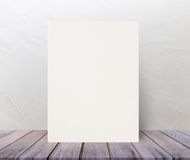 Cartaz de papel texturizado eco em branco no topo de mesa de madeira na parede de cimento branco