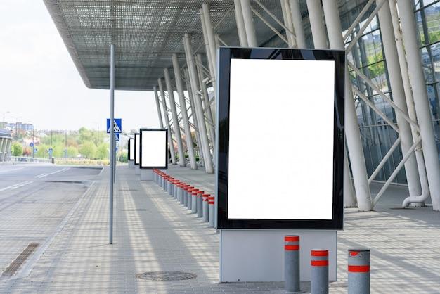 Cartaz de publicidade ao ar livre ao lado das colunas de um edifício moderno.