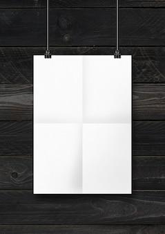 Cartaz dobrado branco pendurado em uma parede de madeira preta com clipes.